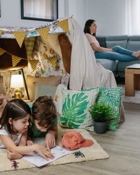 Why Stay at Home Moms Should Cancel Netflix featured image - Children playing camping at home while their mother watches TV sitting on the sofa