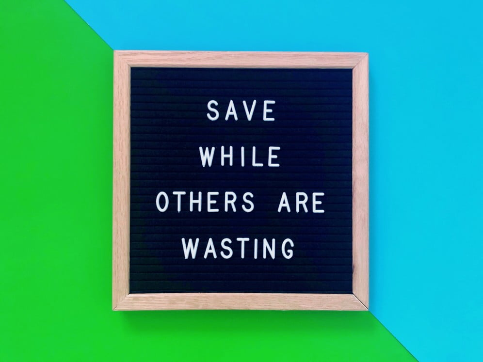 Sign that says save while others are spending