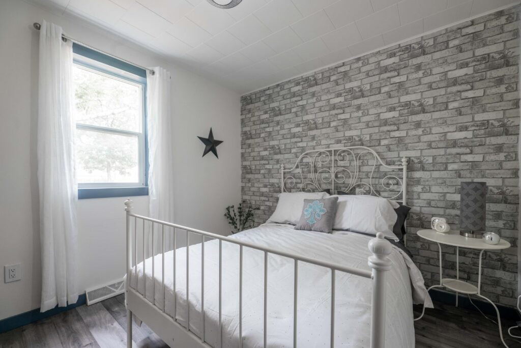 bedroom with grey and white brick wall
