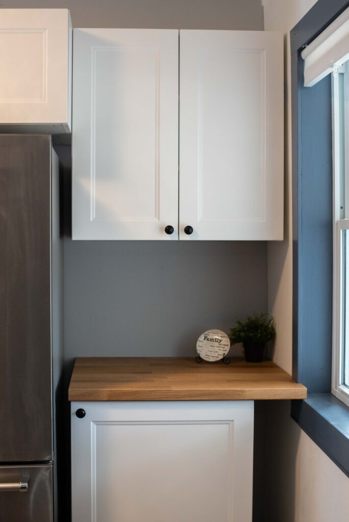 small cupboard and countertop positioned between the fridge and wall