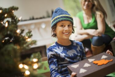 Christmas Gift Ideas for Boys - Featured image of a boy holding a Christmas gift