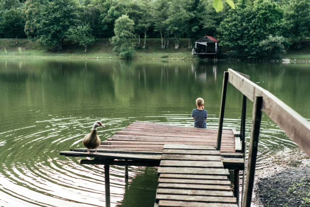 Child sitting on the end of a wooden dock on a lake
