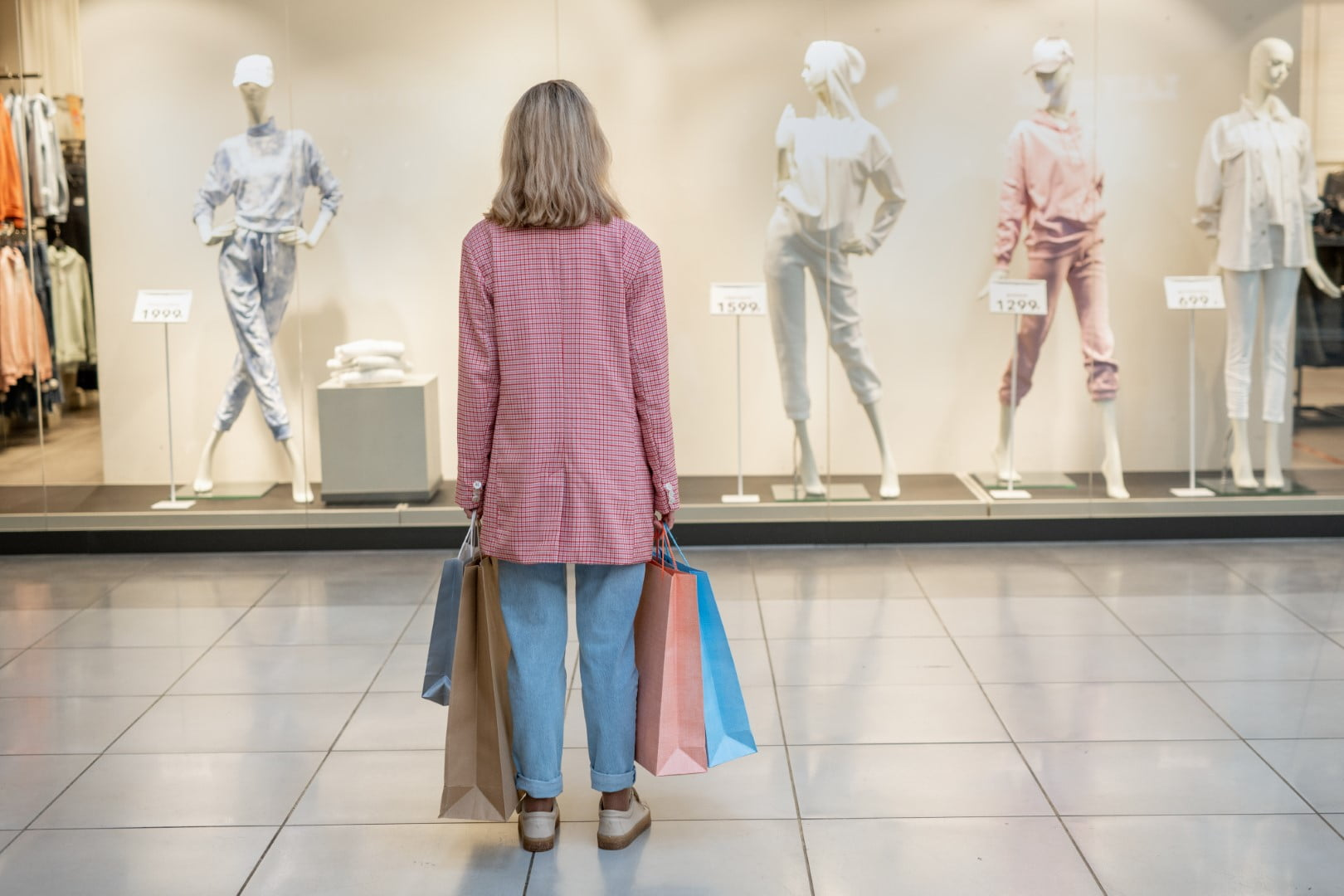 How to Dial Back Your Spending - featured image of a woman standing in a store