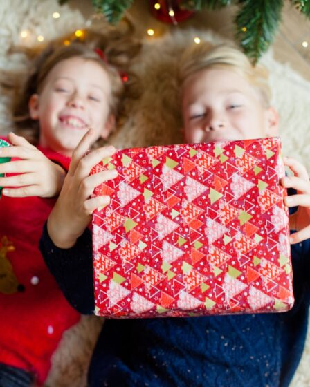 How to Christmas Shop Under $50 Per Kid (in Total) featured image - shows two children laying on the ground holding Christmas presents