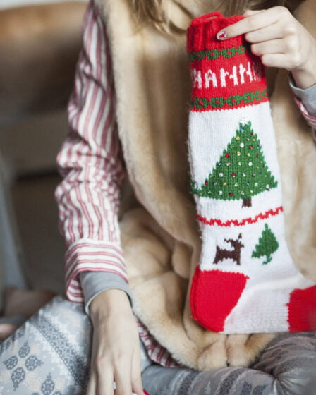 Featured image for Stocking Stuffer Ideas for Mom - shows a woman in pyjamas holding a Christmas stocking