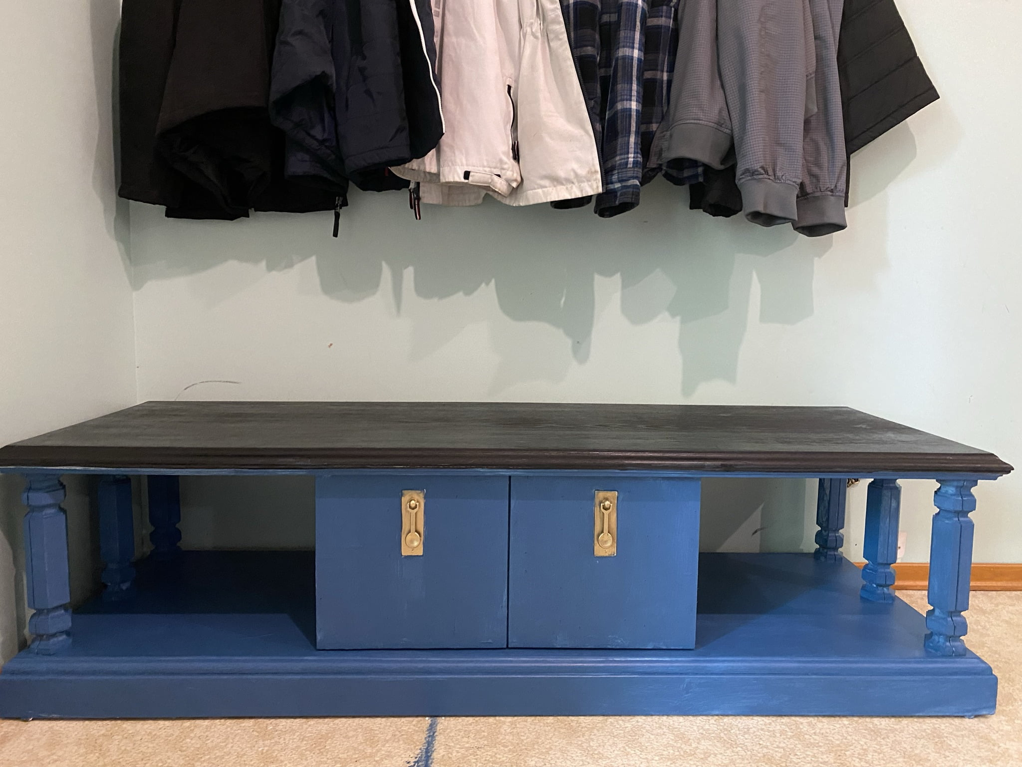 Upcycled TV Stand Turned Into Bench feature image of a blue tv stand with black top under a coat rack